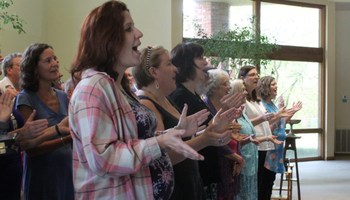 A choir singing in church while clapping their hands